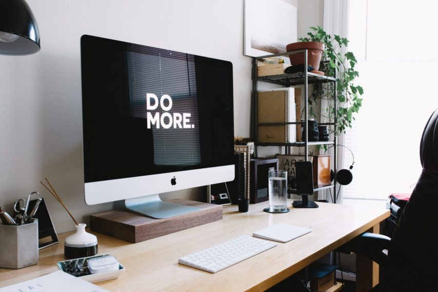 """An iMac on a desk with the words """"do more"""" on the screen"""